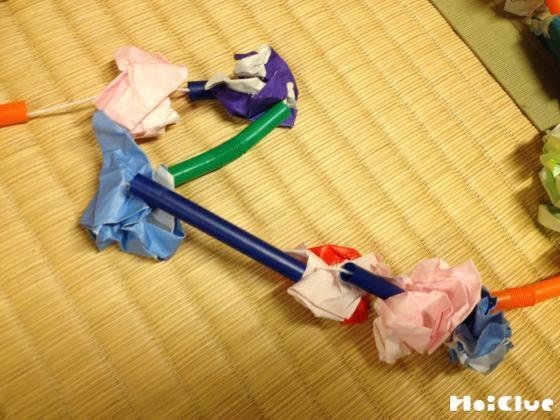 丸めた折り紙とストローを交互に糸に通す様子