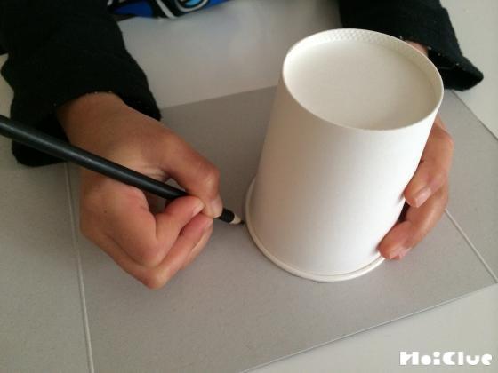 紙コップを底をあてて画用紙に丸を描いている写真