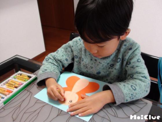 画用紙に貼ったちょうちょに絵を描く子どもの様子