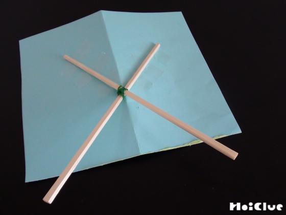 ちょうちょを描いた画用紙の裏側にバッテンになるよう割り箸を固定する様子