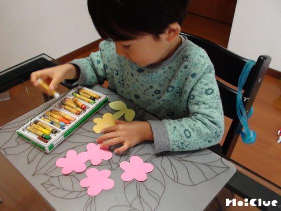 お花形に切った画用紙に絵を描く子どもの様子