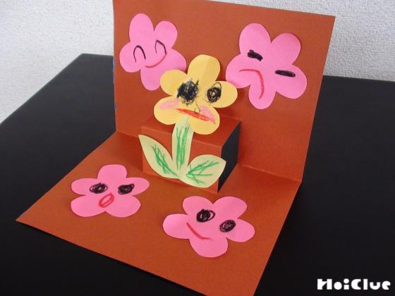土台の画用紙に花を貼り完成した立体カードの写真
