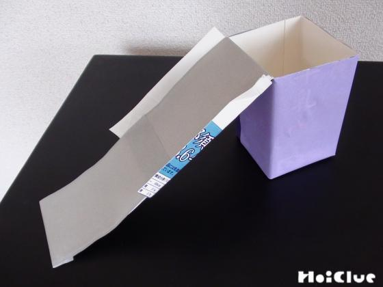 牛乳パックに折り紙を貼り滑り台の手すりを付けた様子