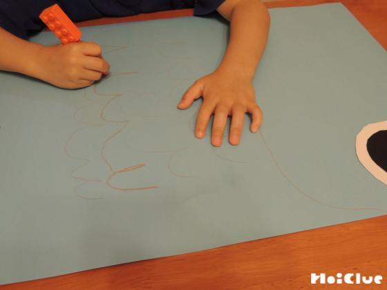 クレヨンで模造紙に絵を描いている写真