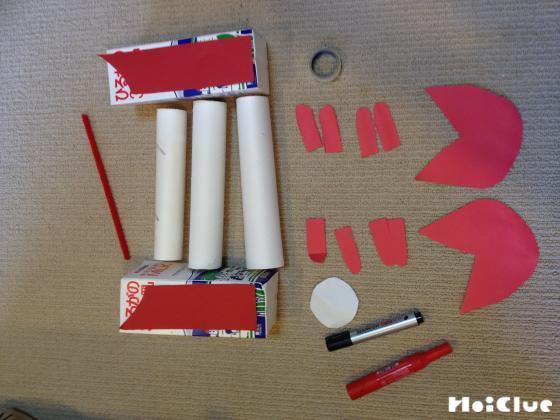 2個の牛乳パックに赤い画用紙を貼りカニのハサミを作る様子