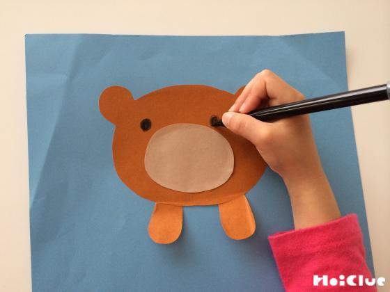 画用紙に動物の顔を描いている写真