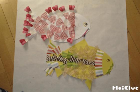 魚の切り抜きに鱗のように切ったカップケーキを貼り付けている写真