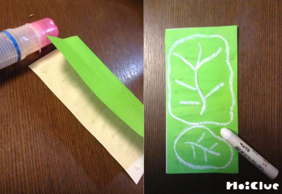 折り紙に葉っぱの絵を描いて半分に折っている写真
