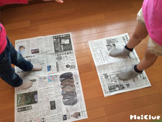 新聞紙の上に立ってじゃんけんしている写真