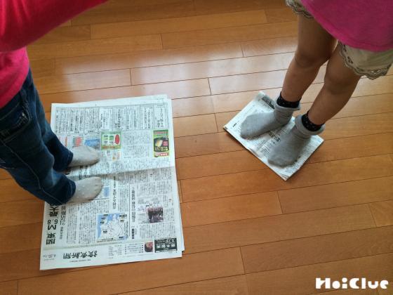 小さくなった新聞紙の上に立ってじゃんけんしている写真