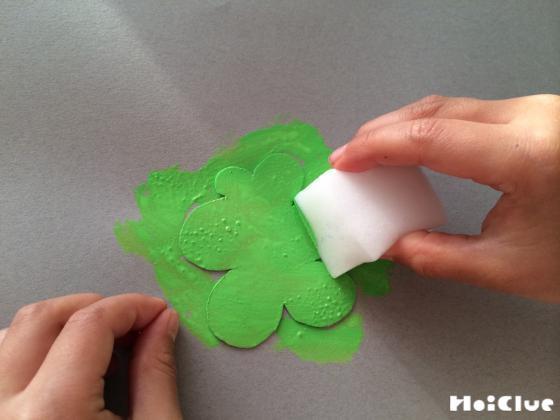 切り抜いた厚紙を画用紙の上にのせて上から色をつけている写真