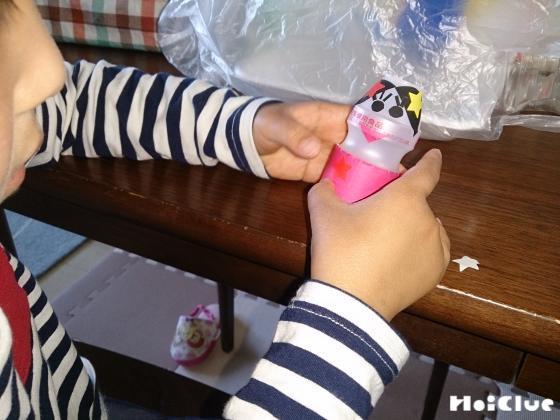 乳酸菌飲料の容器にパーツを貼る子どもの様子