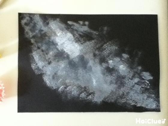 黒い画用紙にポンポンと絵の具で色をつけた写真