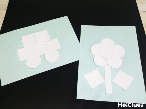 切り抜いた厚紙を並べて車やお花の絵にして貼る様子