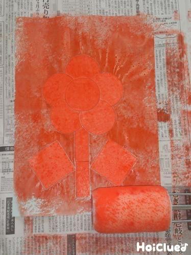 厚紙の絵にローラー刷毛で絵の具をのせていく様子