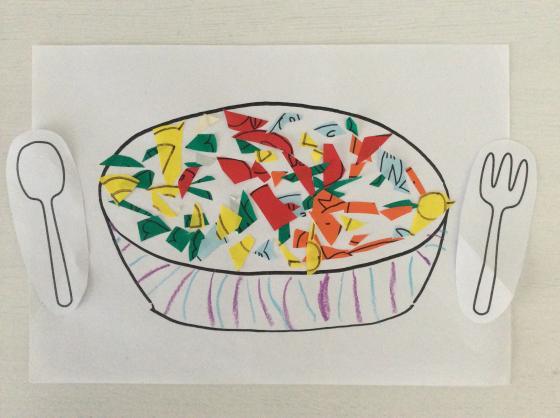 白い画用紙に描いたお皿のなかに色とりどりの折り紙を細かく切ったものを入れた写真