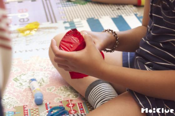 紙コップのまわりに赤いセロファンを貼る子どもの様子