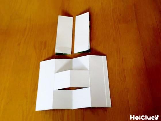 切り込みを入れた方を開き真ん中にできた切れ目に、二つ折りにした残りの牛乳パックを差し込む様子