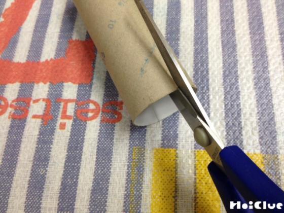 トイレットペーパーの芯の穴の両サイドにハサミで切りこみを入れる様子
