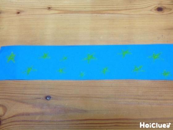 画用紙を帯状にして星の絵を描いている写真