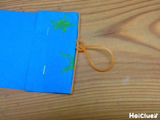 帯にした画用紙を折り返して輪ゴムを通しホチキスで留めた写真