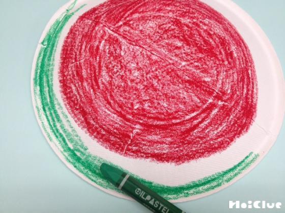 紙皿にスイカの絵を描く様子