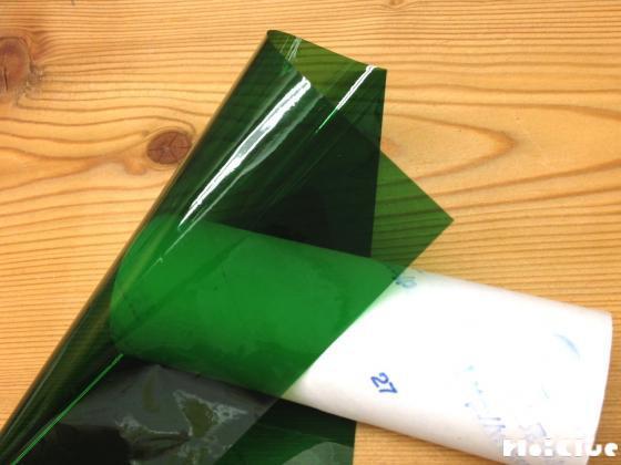 トイレットペーパーの芯の片方の穴にカラーセロファンを貼り付ける様子