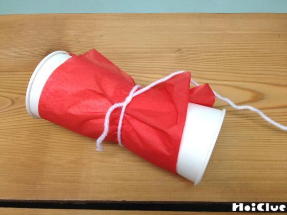 紙コップの側面に花紙を巻き真ん中を毛糸で縛った様子