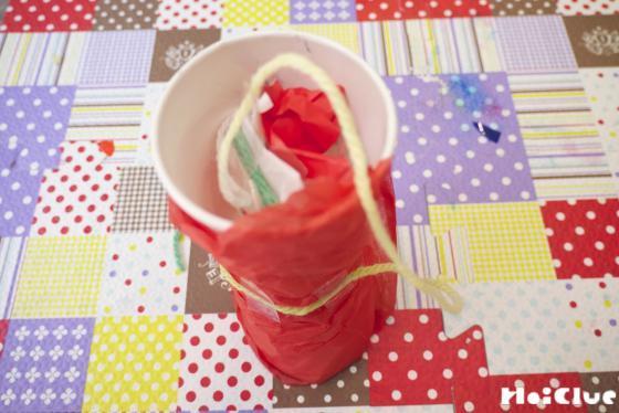 毛糸の先に付けた花紙の玉を紙コップの中に入れた写真
