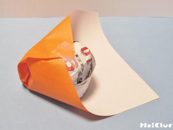 丸めた新聞紙を折り紙で包んでいる写真
