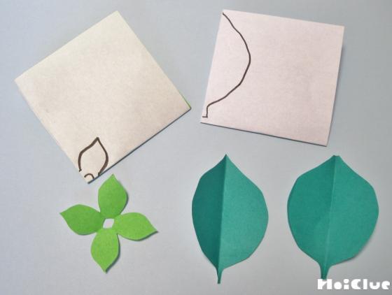 折り紙に折り目をつけて葉っぱの絵を描き切り取った写真