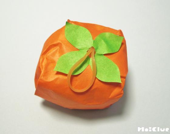 折り紙で包んだ丸い柿に葉っぱをのせ輪ゴムで留めた写真