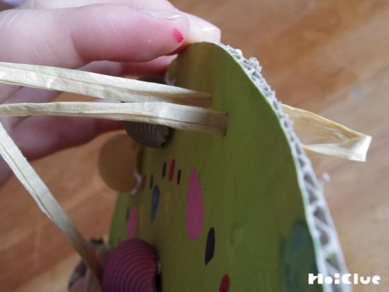 ドーナツ型の台紙に紐を通している写真