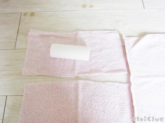 ハンドタオルの上にトイレットペーパーの芯を置いた写真