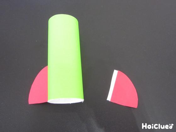 折り紙を貼り付けたトイレットペーパーの芯の両サイドに、ロケットの羽を取り付ける様子