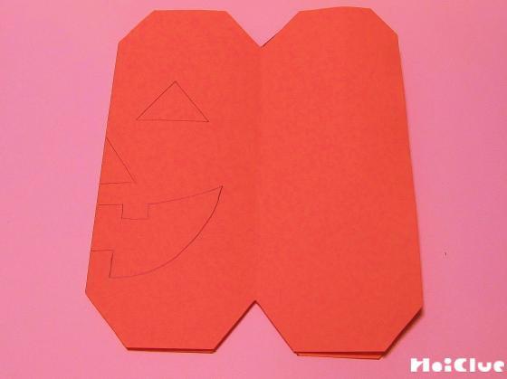 四隅を切り取った画用紙にジャックオーランタンの顔を描いた写真