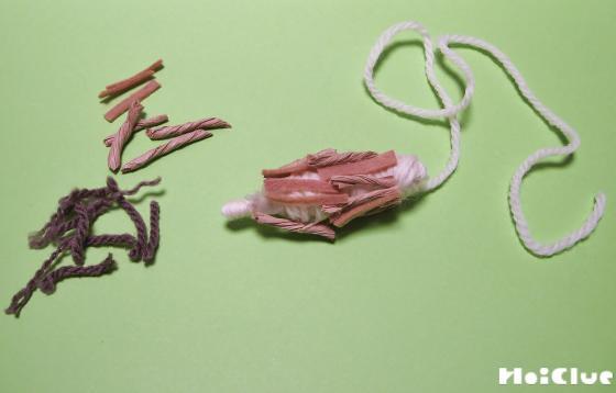 巻きつけた毛糸に茶色い切れ端や毛糸を貼り付けた写真