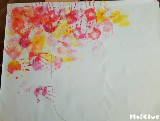 手形を木の葉と見立てて赤や黄色の絵の具で色をつけた写真