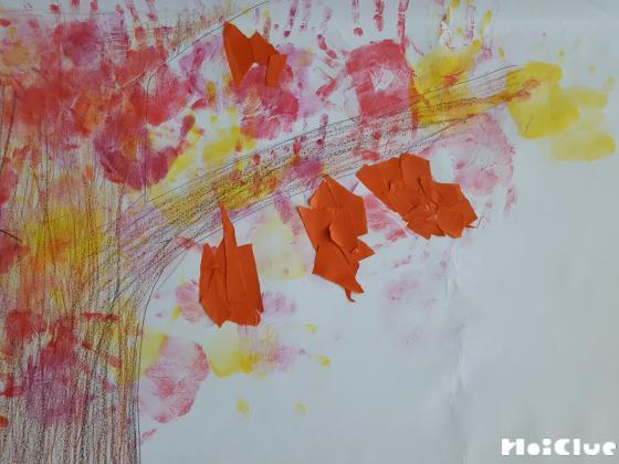 木の幹に色をつけ、茶色い破いた折り紙をミノムシのように貼り付けた写真