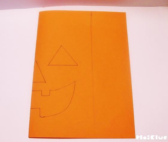 画用紙を二つに折りジャックオーランタンの絵を描いている写真