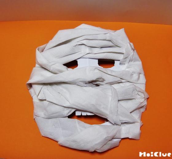 顔の形に切り抜いた厚紙にトイレットペーパーを巻きつけている写真
