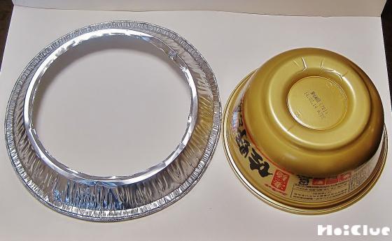 カップ麺の容器と、ドーナツ状にくり抜いたアルミの皿の写真