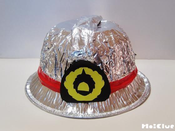 アルミホイルで巻いたティッシュを帽子上部に縦に貼り付け、エンブレムと赤いテープで飾り付けた様子
