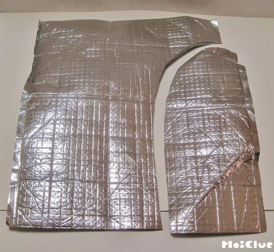 銀色の保冷パックを大きな包丁のような形に切り取る様子