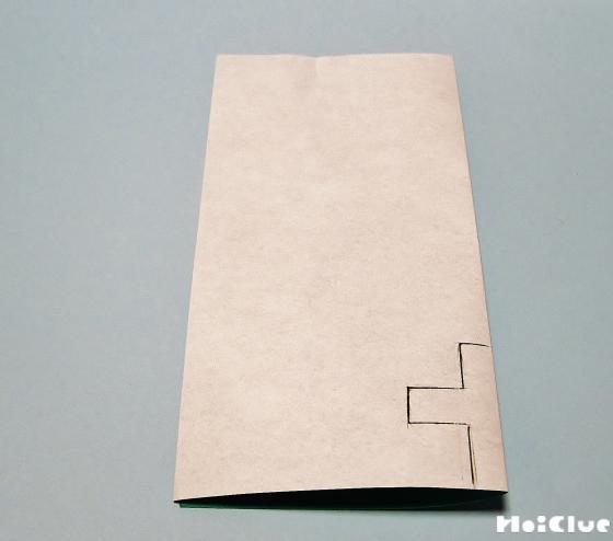 画用紙に十文字を描いている写真