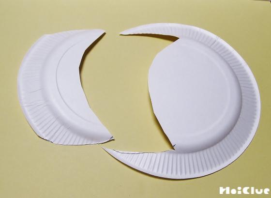 もう一つの紙皿を切り取ってツバの部分を作っている写真