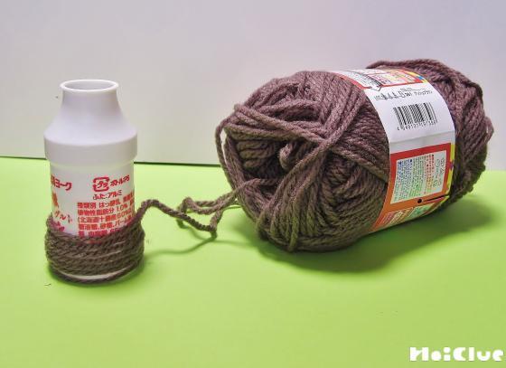 容器に茶色い毛糸を巻いている写真