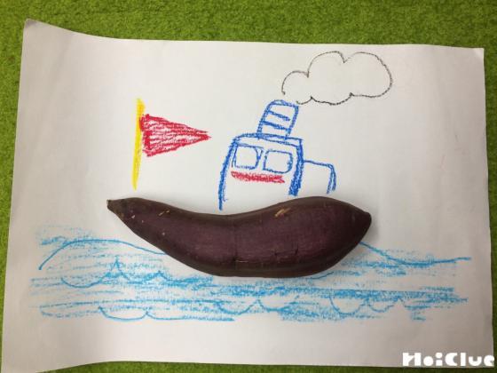 海に浮かぶ船の絵の船の部分にさつまいもを置いた写真