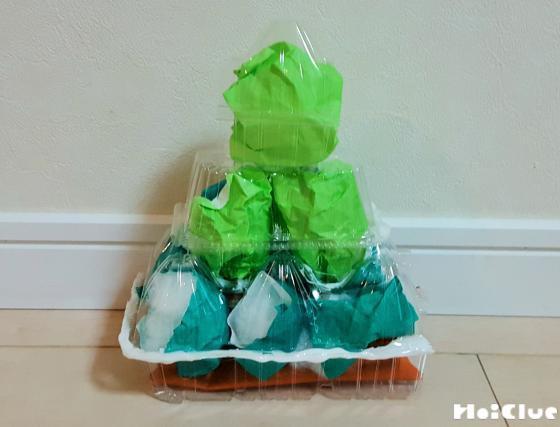 卵パックの窪んだ部分に緑色の折り紙を丸めて入れ木の形になるように重ねた写真