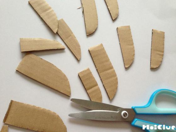 包丁のような形に段ボールを切りカブトムシの身体のパーツを作る様子